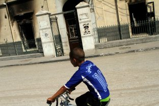 A kid passes by the burnt nuns school were someone sprayed graffiti denouncing the supreme army leader EL-Sisi.