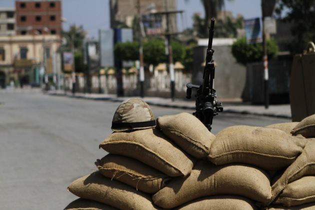 A helmet and a weapon of the Egyptian security forces are placed at a barricade as they prepare to watch the area in Beni Sueif.