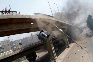 A police vehicle is pushed off of the 6th of October bridge by protesters close to the largest sit-in by supporters of ousted Islamist President Mohammed Morsi in the eastern Nasr City district of Cairo, Egypt, Wednesday, Aug. 14, 2013. Egyptian police in riot gear swept in with armored vehicles and bulldozers Wednesday to clear the sit-in camps set up by supporters of the country's ousted Islamist president in Cairo, showering protesters with tear gas as the sound of gunfire rang out. (AP Photo/Sabry Khaled, El Shorouk Newspaper)