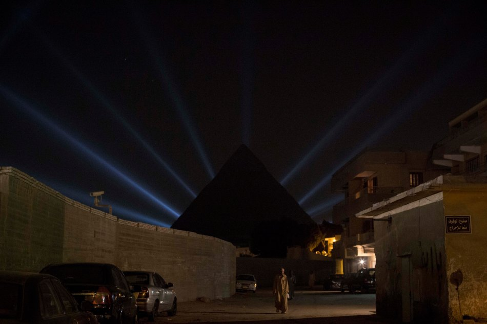 © Sabry Khaled A man passes near The sound & light show as the closing ceremony of Sama'a international spiritual music festival in the Pyramids of Giza. Egypt. (27th of September 2014).